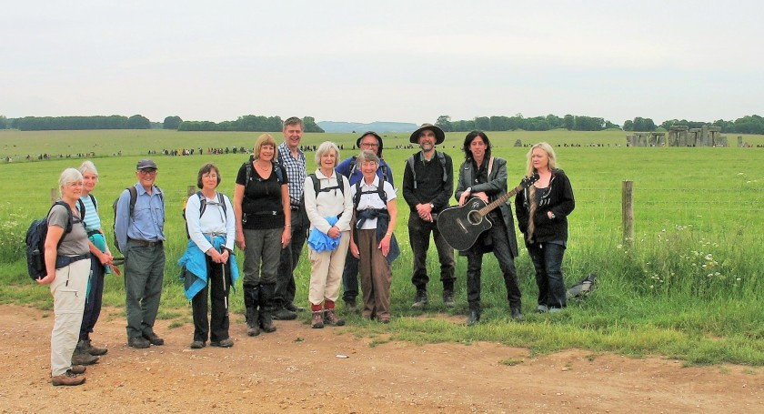 Longer walk group gather in front of the stones at Stonehenge-joined on right by a couple of travellers!
